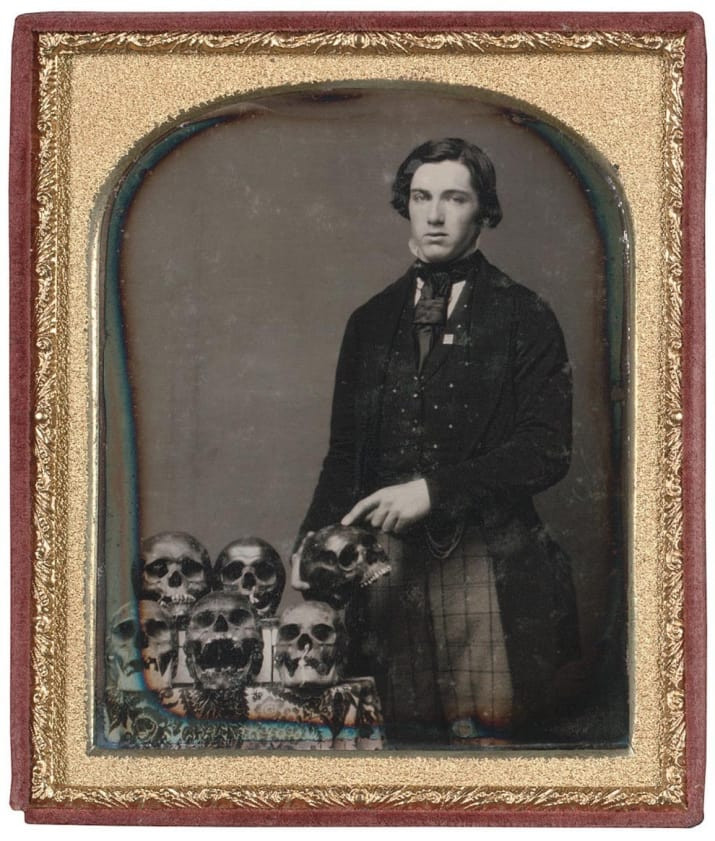 black and white photo of young man posing with six human skulls