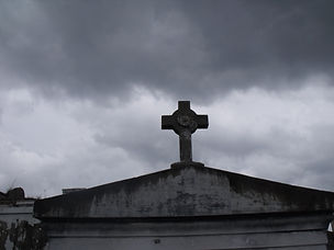 Cloudy skys beyond a cross at the top of a mausoleum in St Louis #1 cemetery