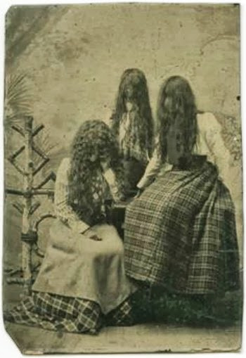 old black and white of three women in plaid skirts and long hair combed over their faces