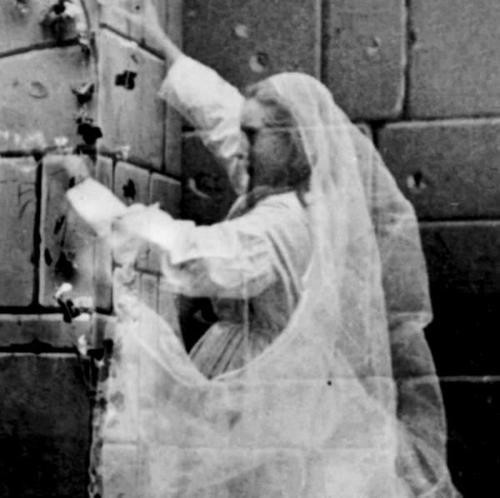 Black and white photo of a young see through girl in a veil touching a brick wall