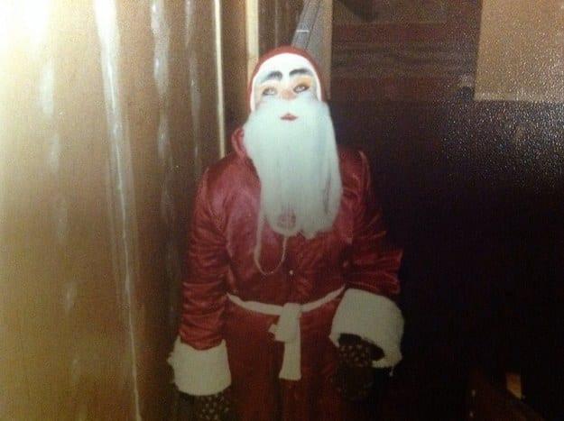 bad santa  person in a creepy mask and a shiny santa suit