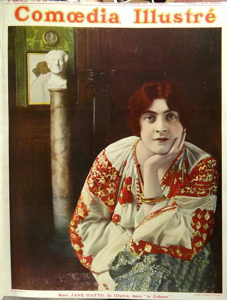 Jane Hatto, a White woman with scarlet hair and lips stares at the viewer. She is dressed in a flowing white, red and green patterned robe with a single heavy gold bangle; and is sat forward, leaning elbow on knee and chin cupped in hand. She sits in a lush room with wood panelling, a bust and painting in the background. This photo is the cover image of the magazine Comoedia Illustre - the title sits at the top of the image in bold red and yellow.