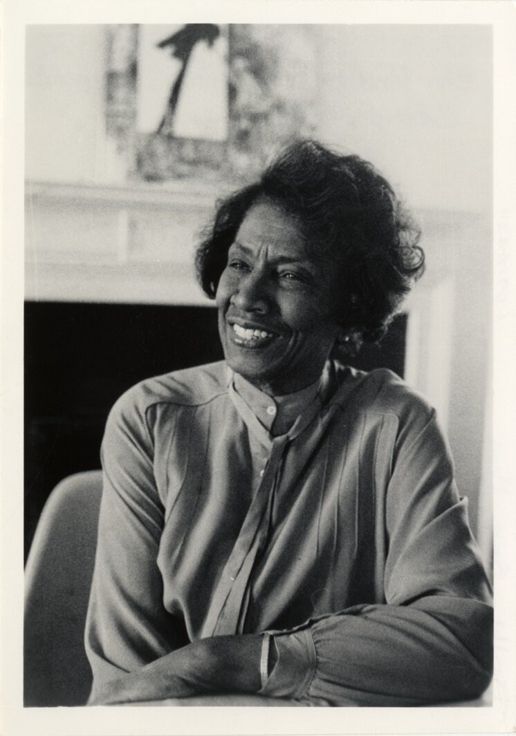 Undine Smith Moore, a Black woman casually leans her left elbow on a table and looks off camera, to the left. She has a broad, warm smile and short black hair, and wears a flowing, high-necked blouse. The image is sepia toned.