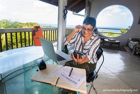 A professional woman smiles while looking at her phone and laptop as she works from a table during her workcation in the Caribbean island of Tobago