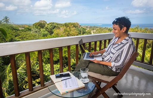 Businesswoman works remotely on her laptop from a balcony of an apartment with a view to the Caribbean Sea in Tobago