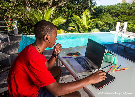 Young student speaks to his teacher during an online class on his laptop poolside at Firefly Villa, Tobago