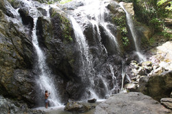 Woman stands under waterfall