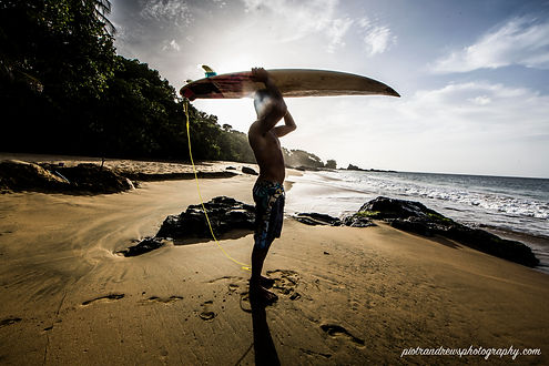 A young man holds his surfboard above his head on the beach in Tobago