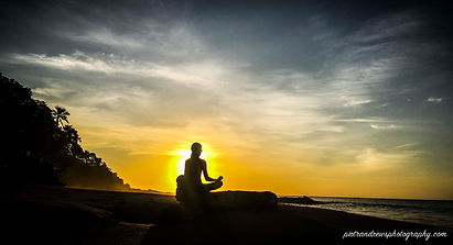 A person is silhouetted as they sit in a lotus position while meditating after doing yoga on Grafton beach Tobago during sunset