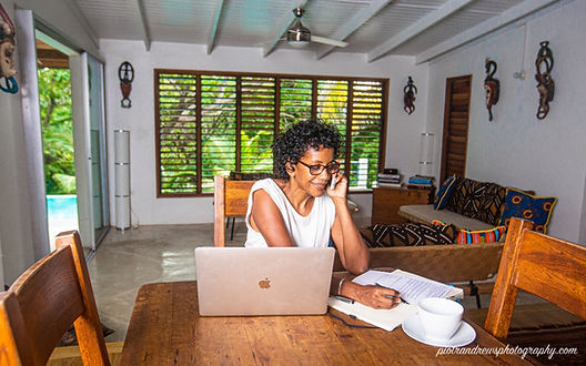 A woman sits at a table while working remotely on her laptop