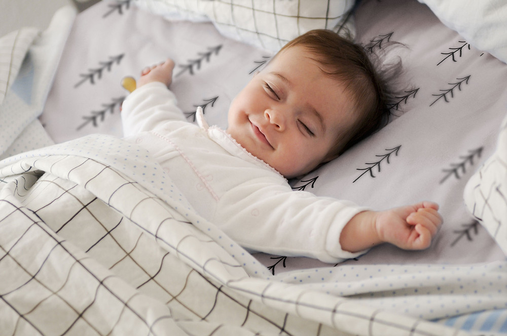 Smiling baby sleeping soundly
