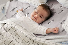 little baby smiling and asleep in a Rockababy Rentals cot while on holiday in Queenstown New Zealand
