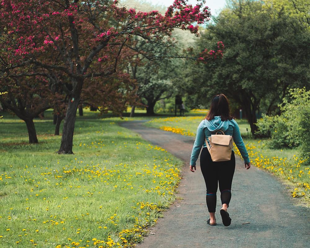 Young woman walking through park