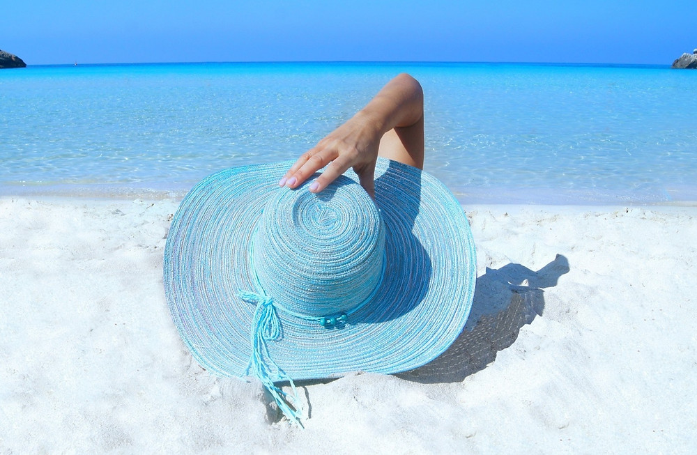 Person lying on beach wearing a sunhat
