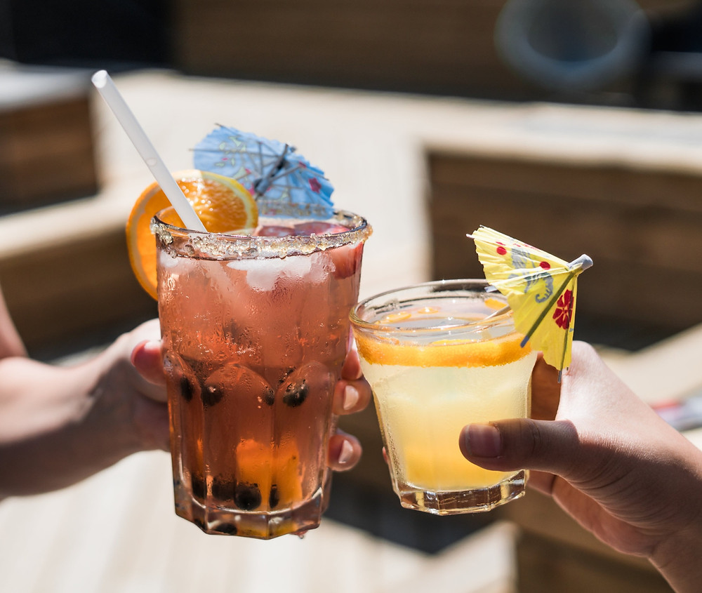 Two hands holing a cocktail each