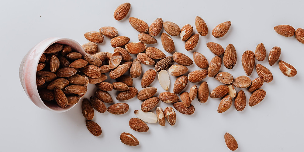 Bowl of almonds emptied onto plain surface