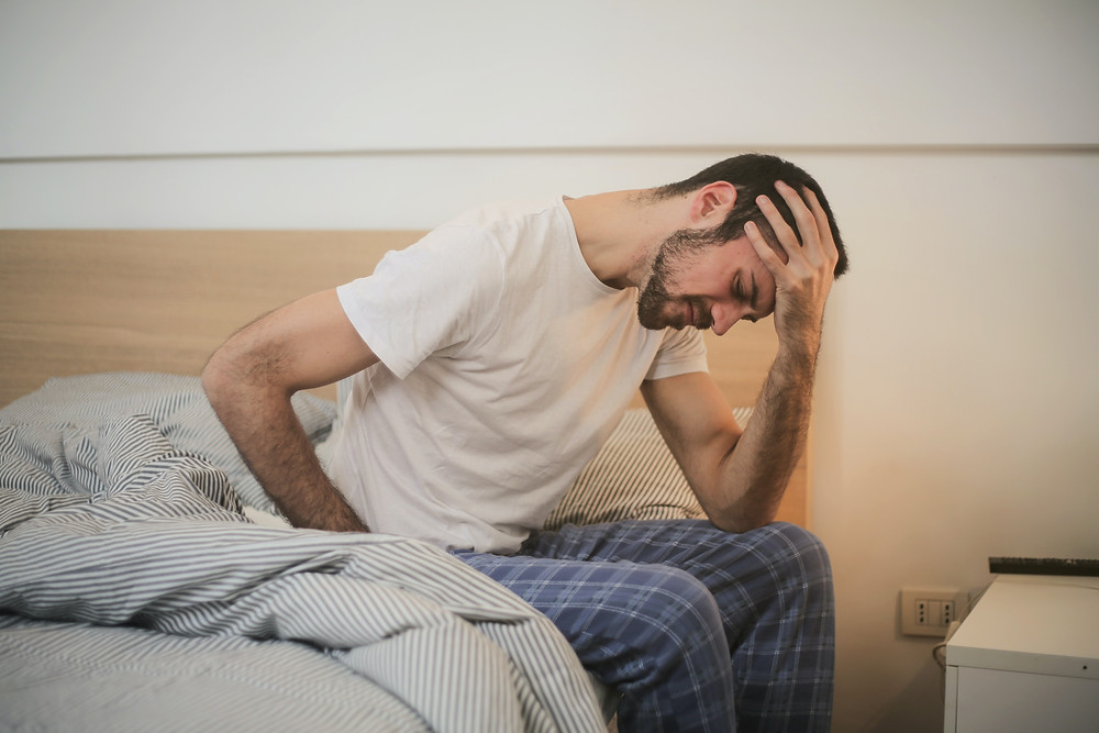 Man in bed with stomach pain