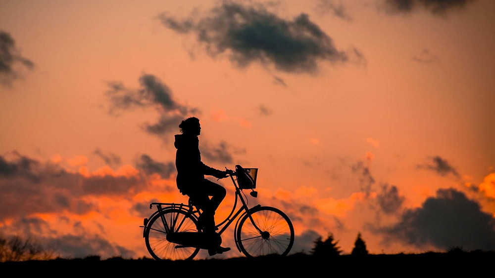 Silhouette of person cycling at sunset