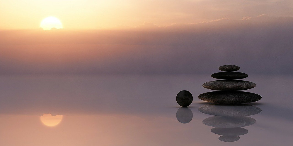 Grey rocks on a body of water during daytime