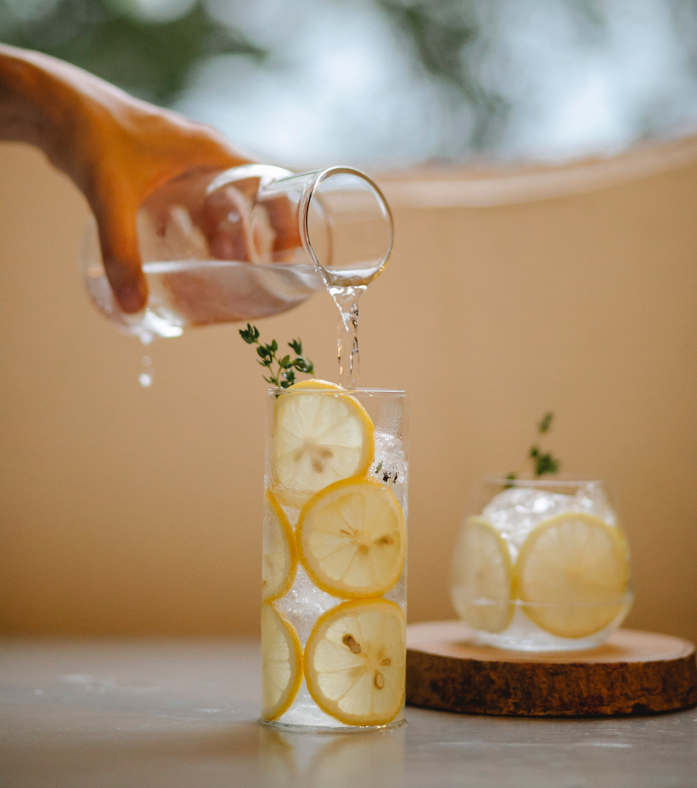 Person pouring water from a jug into a glass with sliced lemons in
