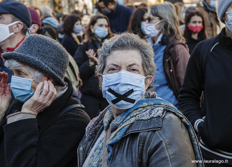 Une femme porte une masque avec une «X» en signe de censure, Marche des libertés, Place de la République 2020. Photo Laura Lago©