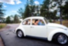 Couple leaving their elopement in their vintage white volkswagon beatle