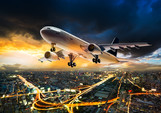 Airplane for transportation flying over the night cityscape on storm cloud in sunset time.