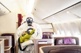 Cleaner officers hold cleaning device on airplane passenger cabin. An employee sprays disi