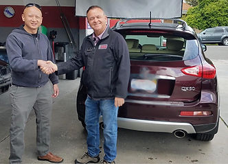 3 Stage Auto Collision owner and client shaking hands upon receiving his fixed Infiniti QX50