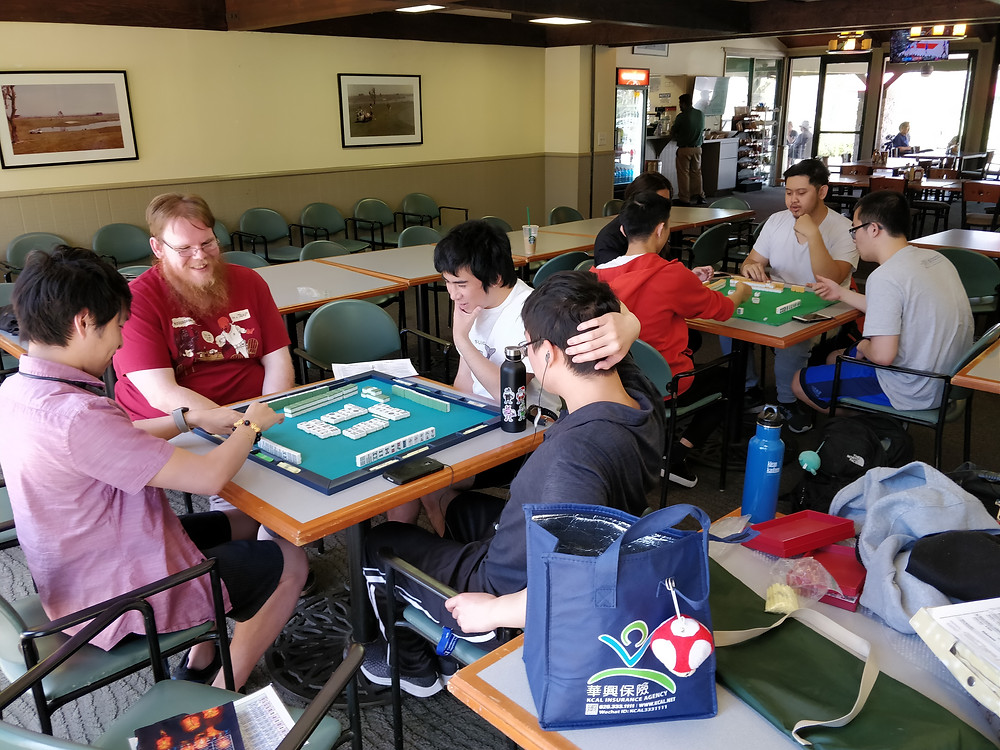 8 players gather around two Mahjong tables during an OC Mahjong Meeting