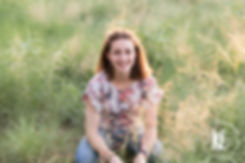 High school senior photo session wit a girl in a grassy field in natural light