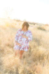 Maternity Photography Shoot in a grassy field with sunset in the background