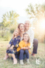 Cute family photo session at sunset in a grassy field with trees