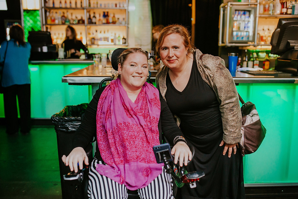 A woman in a power wheelchair, EB Forst, and another woman standing by her side. EB is wearing a bright pink scarf and black and white striped pants.