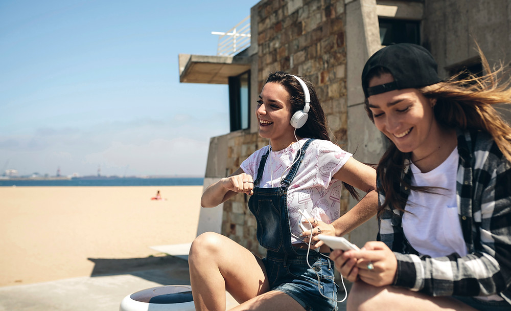 teen girls smiling and listening to music