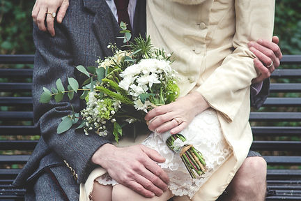Detail of wedding bouquet with brideand groom sitting on bench