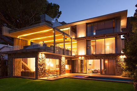 a modern house light up at night that has a living room addition built onto the back