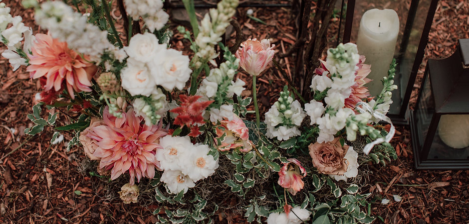A naturalized arrangement of copper, coral and white flowers fom a woodland floral installation for a Catskills wedding at Roxbury Barn and Estate. Floral by Idyllwild Event Design. Photo by Ryan Elizabeth Photography.