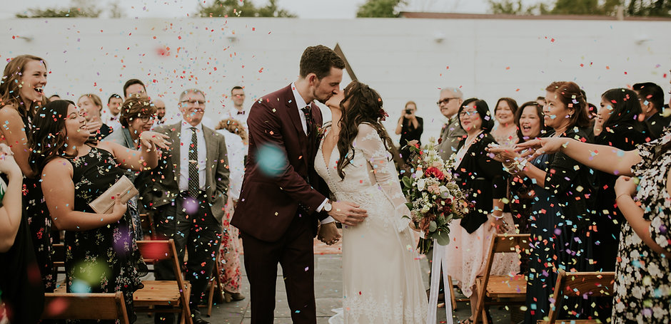 Hudson Valley bohemian wedding at Audrey's Farmhouse and the Greenhouses Hotel. Bride and Groom kiss as guests toss eco-friendly confetti. Photo by Catherine Coons Photography. Floral and Decor by Idyllwild Event Design.