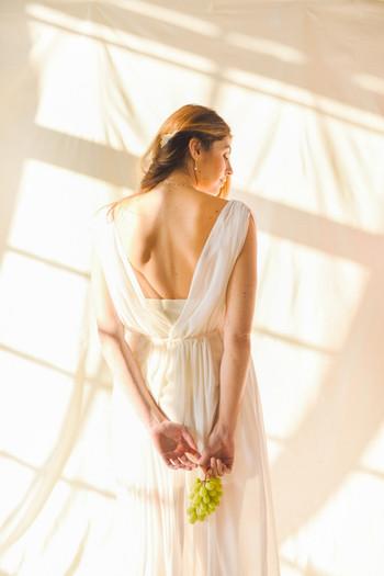 Robe Isadora : plissée en mousseline de soie, cintrée à la taille, décolletée devant et dos. Sous robe Marie Agnes : coupe droite et courte, bretelles en ruban de guipure.
