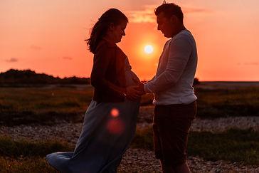 Femme enceinte au coucher du soleil qui se touche le ventre lors d'un shooting photo avec un photographe professionnel En Baie de Somme, entre Abbeville (80) et Eu (76) dans la région des Hauts de France (59, 62).
