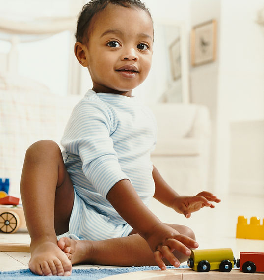 Black Baby sitting while playing with blocks looking towards the table.