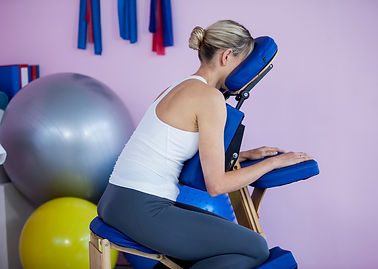 Woman sitting on massage chair in clinic
