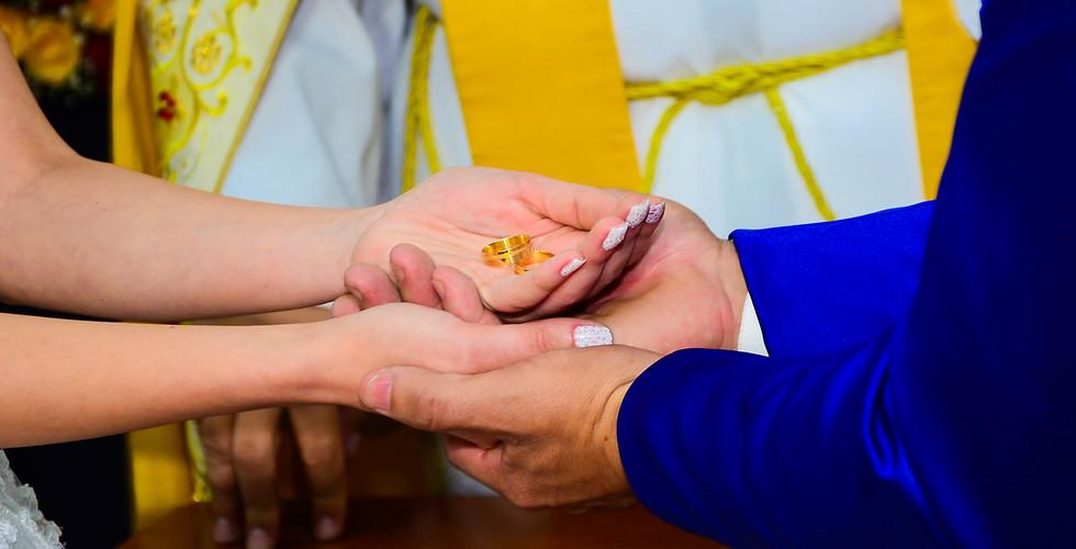 foto dos noivos na igreja segurando aliança