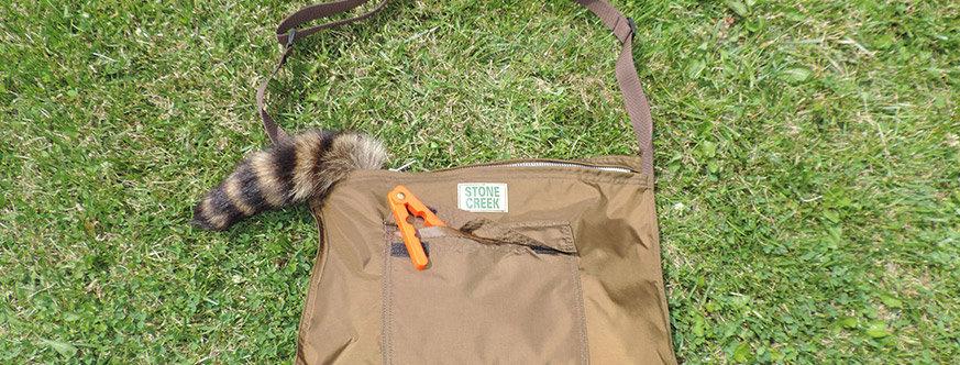brown nylon game bag with front pocket, adjustable shoulder strap, lifetime warranty zipper