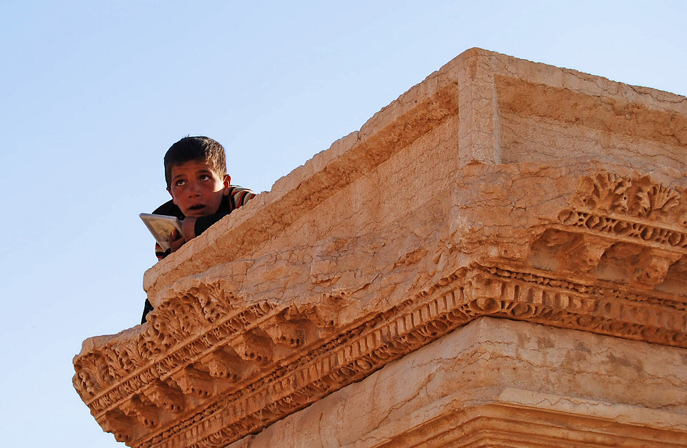Young boy sits atop Palmyran antiquity. Photo: Alessandra Kocman