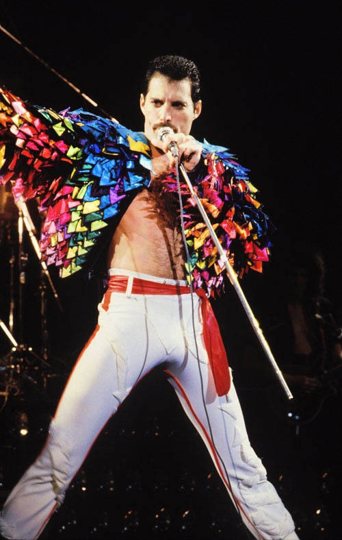 Freddie onstage in just a multicoloured jacket and white trousers.