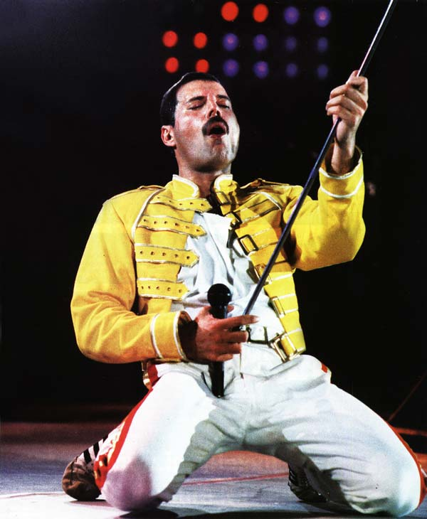 Freddie wearing one of his most iconic outfits, a yellow jacket over a simple white outfit, while onstage.