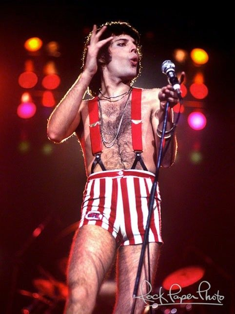 Freddie in a simply flamboyant outfit of striped red booty shorts held up by suspenders.