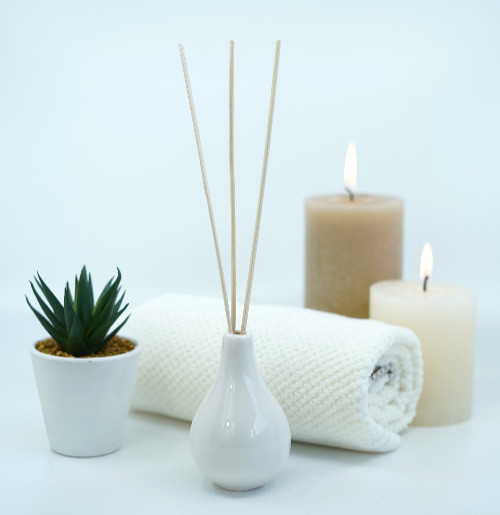 scented candles, diffuser and mini plant pot set up around white towel on white background